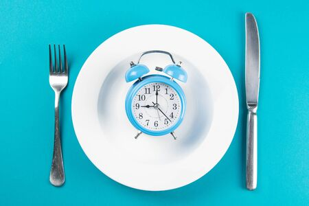 Alarm clock with fork and knife on the white plate on blue table. Time to eat, Breakfast, Lunch Time and Dinner concept. Top wievs