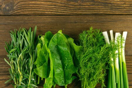 Mixed greens, fresh, garden herbs. Spinach, rosemary, dill and green onions stand on a wooden table. Top views with clear space. Standard-Bild