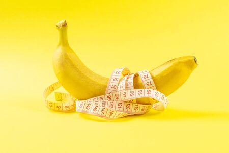 Banana with tape for measuring figure. Centimeter ruler spinned around fruit. Tape wrapped around banana isolated on yellow background. Weight loss, healthy food and slim body concept.