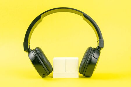 Black headphones and wooden cubes on a yellow background. On cubes you can enter your date, month and day. Stockfoto