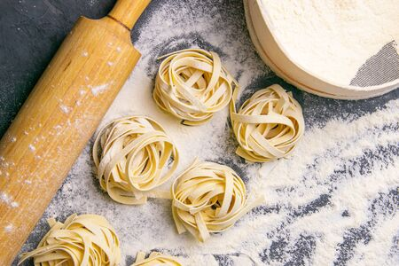 Variety of italian homemade raw uncooked pasta spaghetti and tagliatelle with flour on wooden board with rocking for the dough over black texture background. Flat lay.
