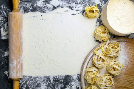 Pasta tagliatelle, eaten for flour and rocking for the dough are arranged so that inside there is a free room for the location of your text. Top views with clear space.