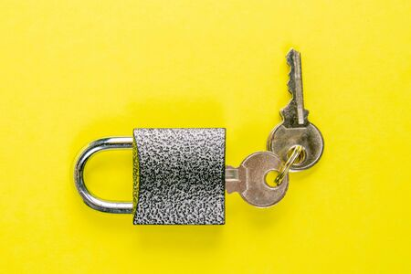 Macro of a locked padlock with the key on yallow background.