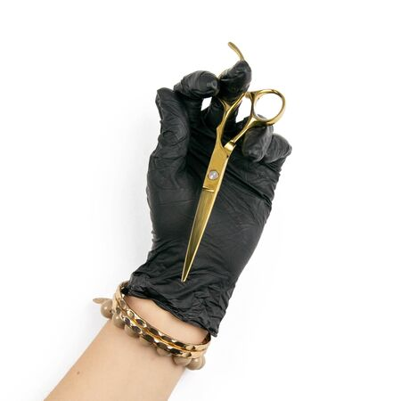 Gloved hand holding a gold scisors on an isolated white background.