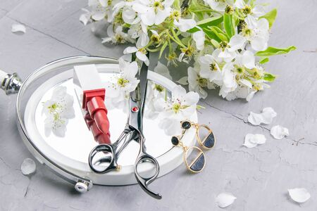 Cosmetic set on grey dressing table. Top views, close-up. Scissors, lipstick and earrings stand on a mirror sprinkled with white flowers.