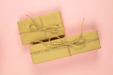 Two gift boxes wrapped of craft paper and burlap ribbon on the pink background, top view, close-up. Banque d'images