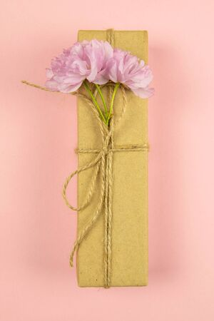 Gift boxes wrapped of craft paper and burlap ribbon with pink flowers on the pink background, top view, close-up. Banque d'images