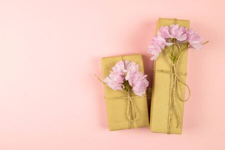 Two gift boxes wrapped of craft paper and burlap ribbon with pink flowers on the pink background, top view with clear space.