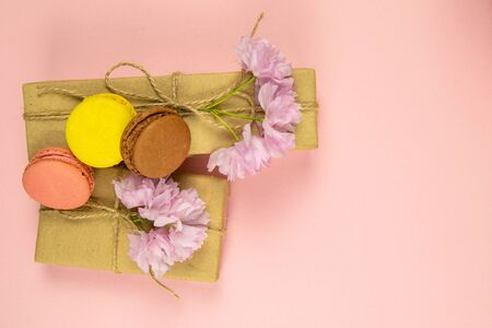Multicolored macaroons with peonies and gift box on Pink table. Top views, close-up.