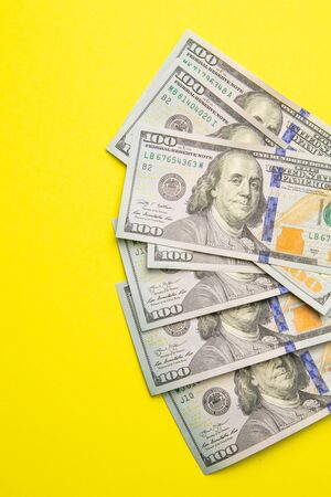 One hundred dollar banknotes on colored background top view, with empty place for your text business money concept, US dollar money cash on yellow background.