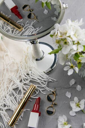 Cosmetic set on grey dressing table. Top views, close-up. Mirror, shadows, lipstick and white flowers.