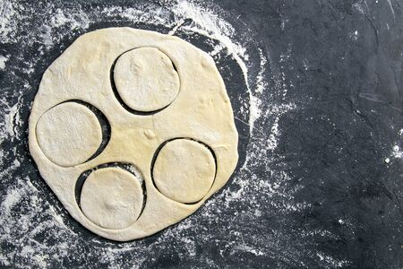 The process of cutting circle from the dough on a dark background. Top views with clear space.