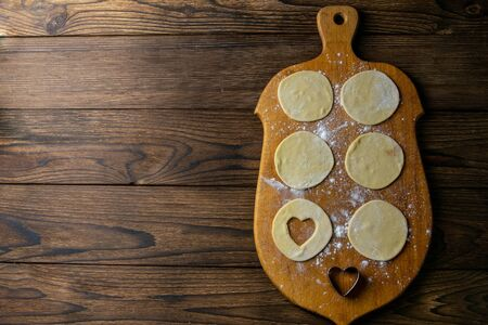 Heart shaped dumplings, flour on wooden background. Cooking dumpling. Top view with clear space.