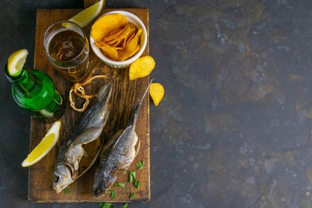 Dried salted crucian with beer, lemon and potato chips on dark wooden board. Snack on fish with beer. Top views with clear space. Banque d'images