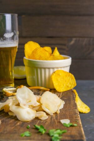 Dried octopus with beer, lemon and potato chips on dark wooden board. Snack on fish with beer. Close-up.