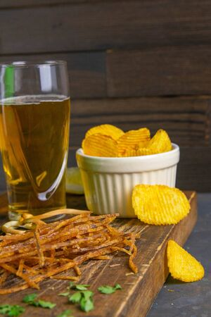 Dried salmon cobweb with pepper with beer, lemon and potato chips on dark wooden board. Snack on fish with beer. Close-up.