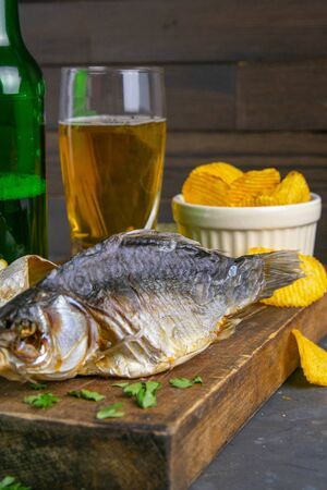 Dried salted crucian with beer, lemon and potato chips on dark wooden board. Snack on fish with beer. Close-up. 版權商用圖片