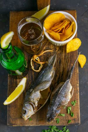 Dried salted crucian with beer, lemon and potato chips on dark wooden board. Snack on fish with beer. Close-up. Banque d'images