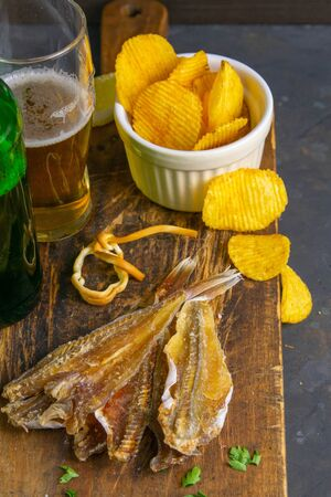 Silver Amber Fish with pepper with beer, lemon and potato chips on dark wooden board. Snack on fish with beer. Front views, close-up.