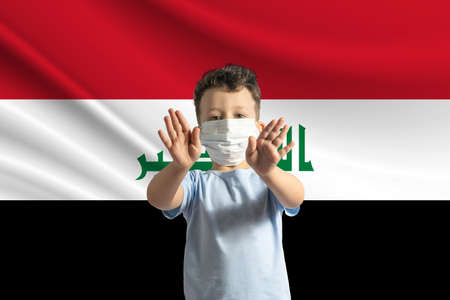 Little white boy in a protective mask on the background of the flag of Iraq Makes a stop sign with his hands, stay at home Iraq.