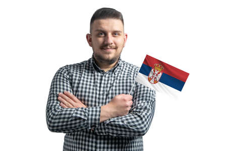 White guy holding a flag of Serbia smiling confident with crossed arms isolated on a white background.