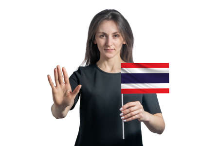 Happy young white woman holding flag of Thailand and with a serious face shows a hand stop sign isolated on a white background.