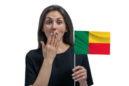 Happy young white woman holding flag of Benin and covers her mouth with her hand isolated on a white background.