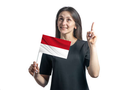 Happy young white woman holding flag of Indonesia and points thumbs up isolated on a white background.