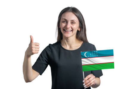 Happy young white woman holding flag of Uzbekistan and shows the class by hand isolated on a white background.