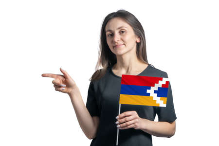 Happy young white woman holding flag Nagorno-Karabakh Republic and points to the left isolated on a white background.