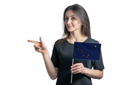Happy young white woman holding flag Alaska and points to the left isolated on a white background.