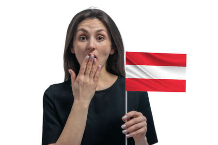Happy young white woman holding flag of Austria and covers her mouth with her hand isolated on a white background.