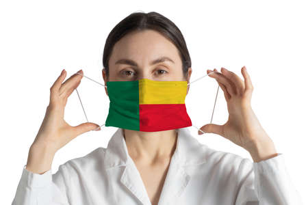 Respirator with flag of Benin Doctor puts on medical face mask isolated on white background. 版權商用圖片