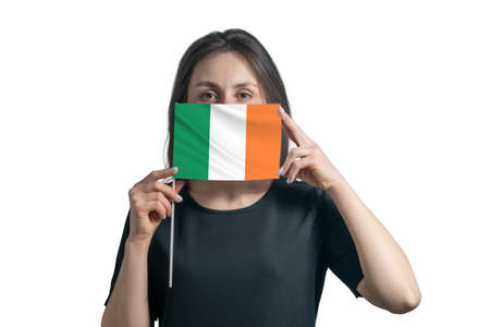 Happy young white woman holding flag Ireland flag and covers her face with it isolated on a white background.