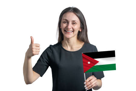 Happy young white woman holding flag of Jordan and shows the class by hand isolated on a white background.