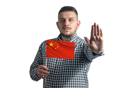 White guy holding a flag of People's Republic of China and with a serious face shows a hand stop sign isolated on a white background .. Foto de archivo