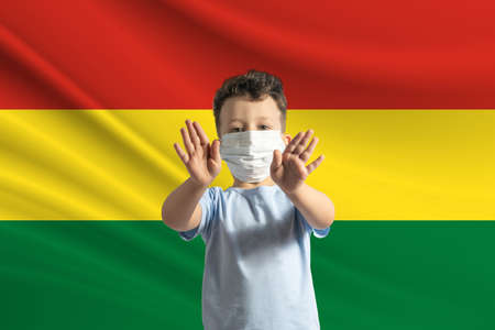 Little white boy in a protective mask on the background of the flag of Bolivia. Makes a stop sign with his hands, stay at home Bolivia.
