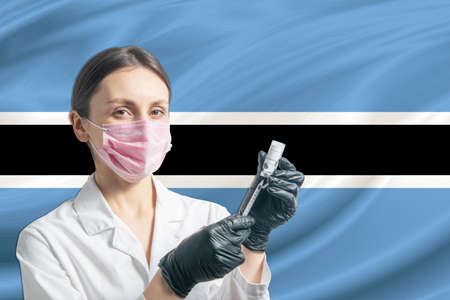 Girl doctor prepares vaccination against the background of the Botswana flag. Vaccination concept Botswana. 免版税图像