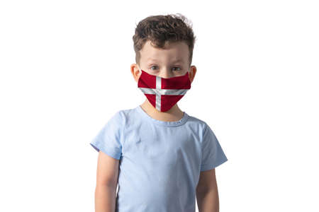 Respirator with flag of Denmark. White boy puts on medical face mask isolated on white background. 免版税图像