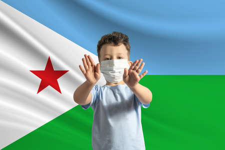 Little white boy in a protective mask on the background of the flag of Djibouti. Makes a stop sign with his hands, stay at home Djibouti.