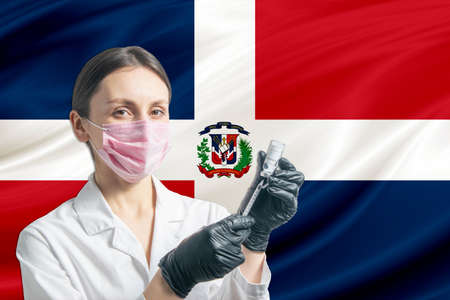 Girl doctor prepares vaccination against the background of the Dominican Republic flag. Vaccination concept Dominican Republic.