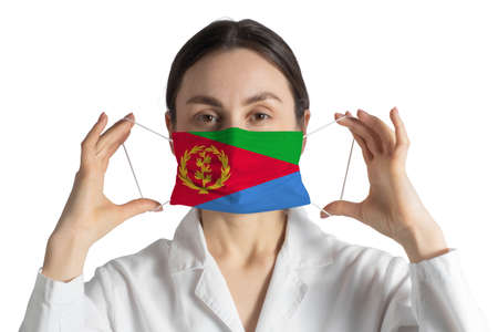 Respirator with flag of Eritrea Doctor puts on medical face mask isolated on white background.