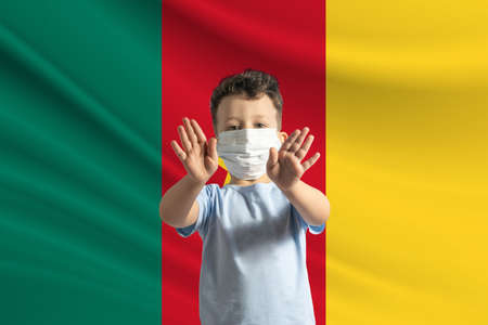 Little white boy in a protective mask on the background of the flag of Cameroon Makes a stop sign with his hands, stay at home Cameroon. 免版税图像