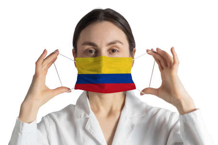 Respirator with flag of Colombia Doctor puts on medical face mask isolated on white background.