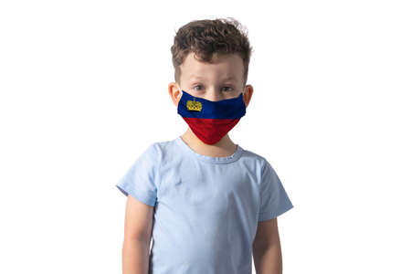Respirator with flag of Liechtenstein. White boy puts on medical face mask isolated on white background. 免版税图像