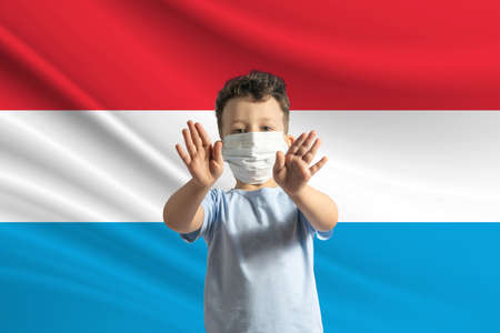 Little white boy in a protective mask on the background of the flag of Luxembourg. Makes a stop sign with his hands, stay at home Luxembourg. 免版税图像
