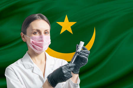 Girl doctor prepares vaccination against the background of the Mauritania flag. Vaccination concept Mauritania.