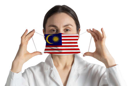 Respirator with flag of Malaysia Doctor puts on medical face mask isolated on white background.