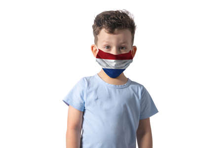 Respirator with flag of Netherlands. White boy puts on medical face mask isolated on white background. 免版税图像