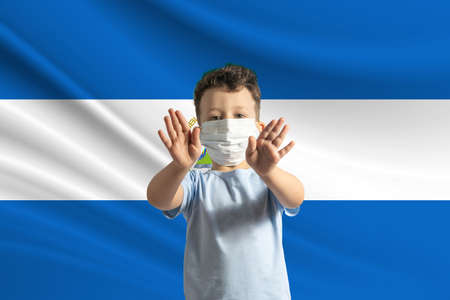 Little white boy in a protective mask on the background of the flag of Nicaragua. Makes a stop sign with his hands, stay at home Nicaragua.